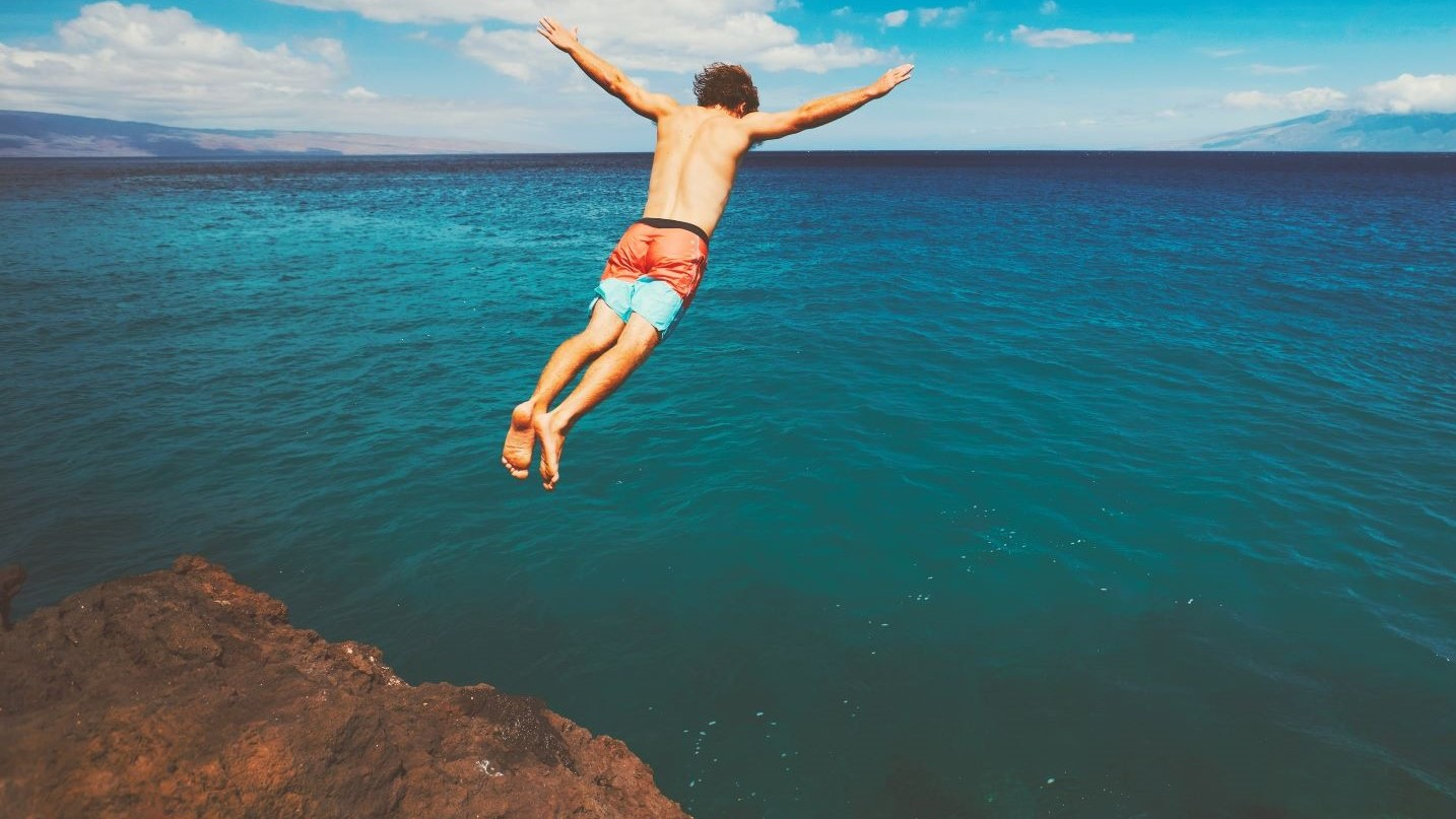 risk-taker-cliff-jumping-into-the-ocean